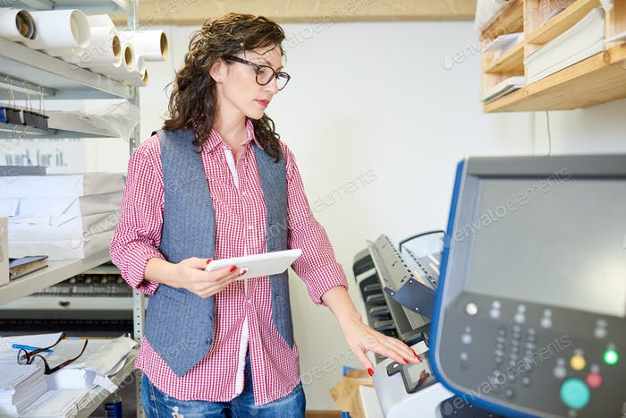 Woman calibrating printer in office