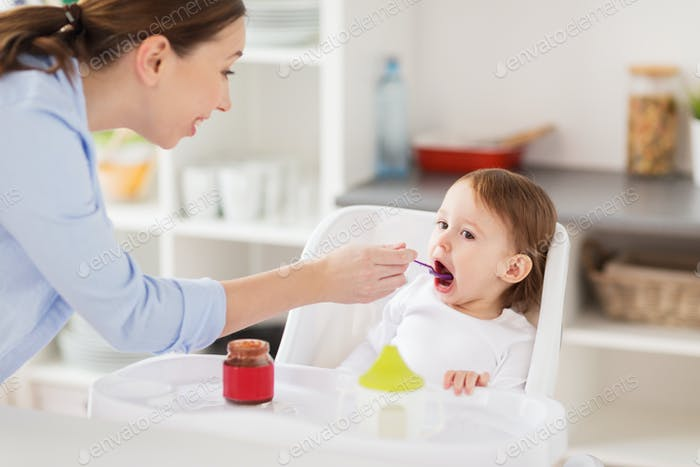 happy mother feeding baby with puree at home