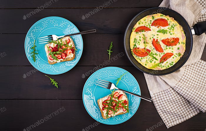 Omelette with tomatoes, ham, green onion and sandwich with strawberry on dark table.