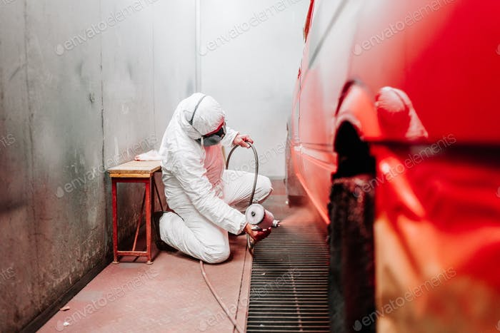 industrial worker, mechanic engineer painter using a spray brush gun and painting a car
