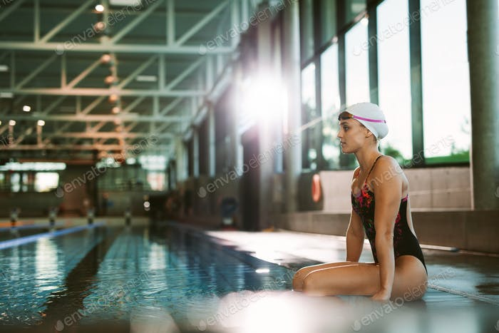 Female swimmer relaxing at the edge of a pool