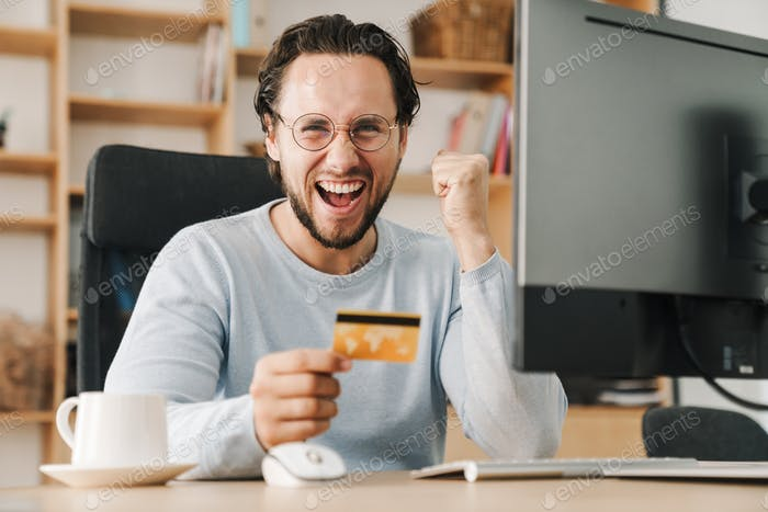 Image of programmer man making winner gesture and holding credit card