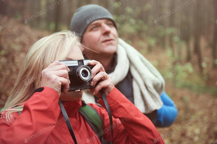Woman taking pictures in the forest
