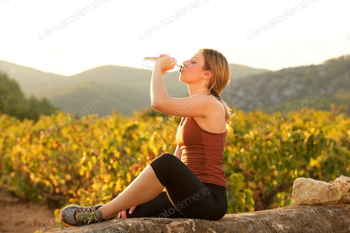 sporty young woman sitting outside drinking water