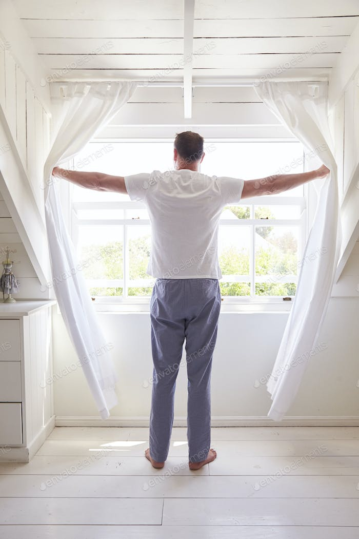 Rear View Of Man Opening Curtains And Looking Out Of Window
