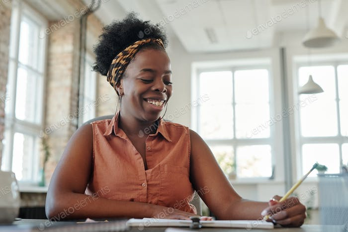 Happy young woman of African ethnicity making notes in copybook by table