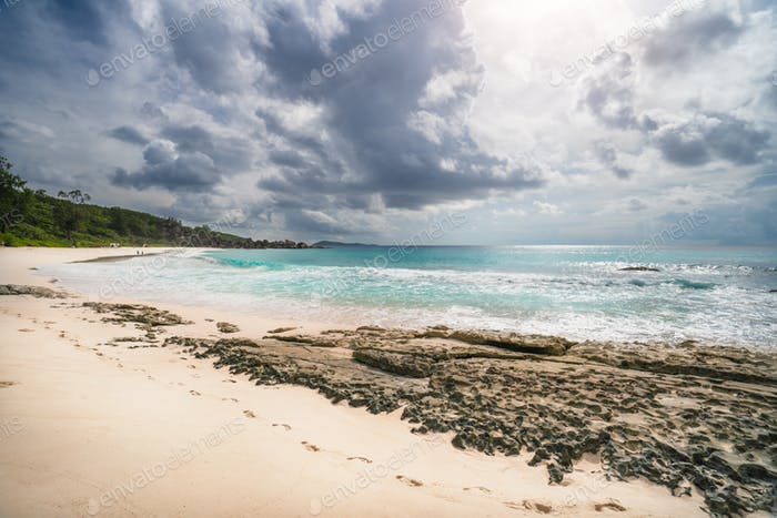Grand Anse beach, Seychelles, La Digue, tropical sandy beach, blue ocean and rainy clouds