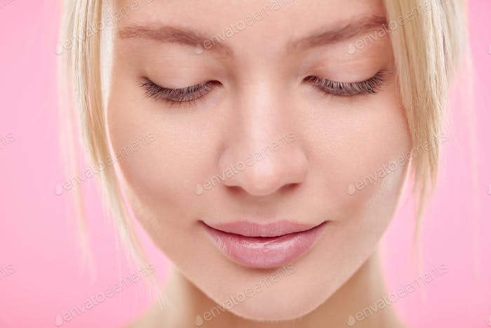 Face of young blond serene woman with natural makeup looking down