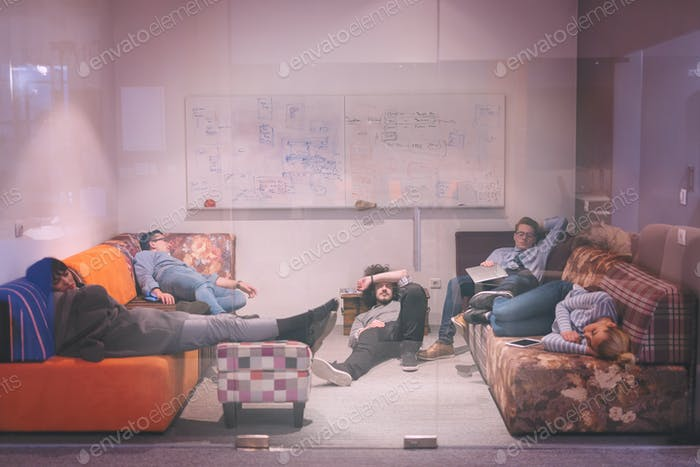 software developers sleeping on sofa in creative startup office