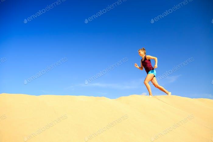 Junge Frau läuft auf Sandwüstendünen