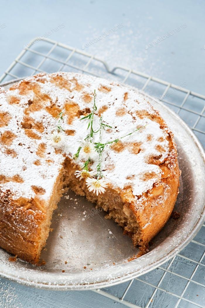 Healthy Wholemeal apple cinnamon tea cake on light blue background.