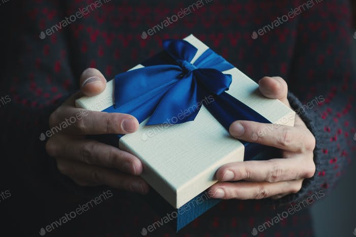 Mann mit schwarzem Pullover hält ein Geschenk mit blauem Band