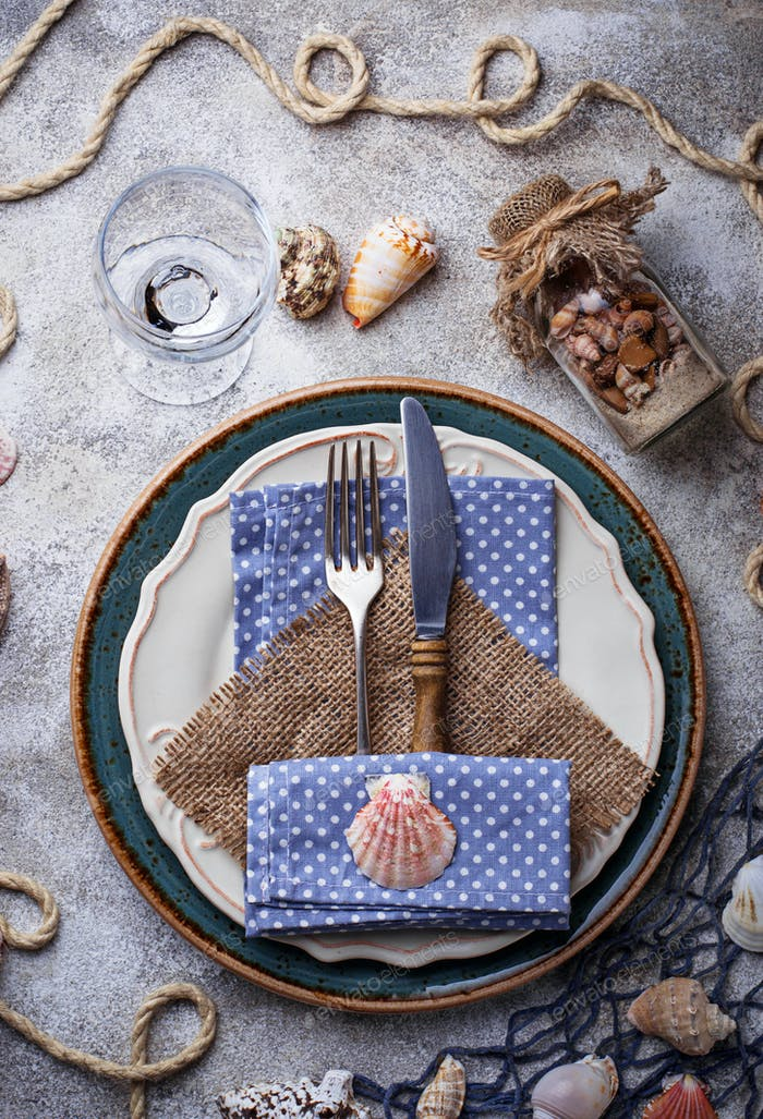 Marine style table setting with sea shells, fishnet and rope