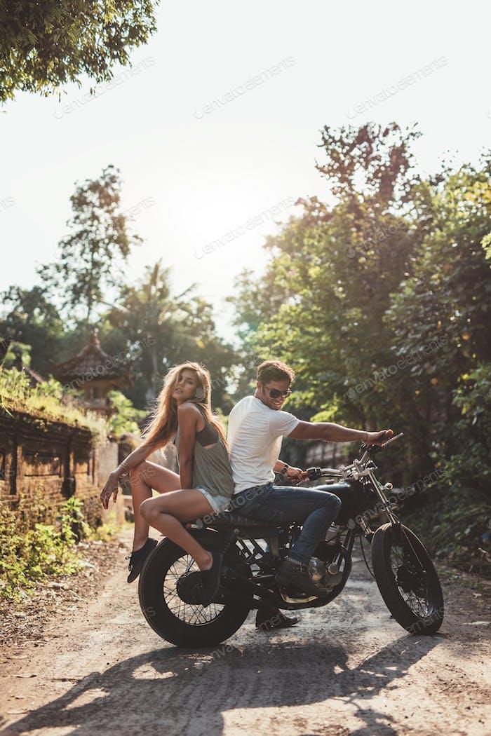 Paar hängen mit Motorrad auf Dorfstraße