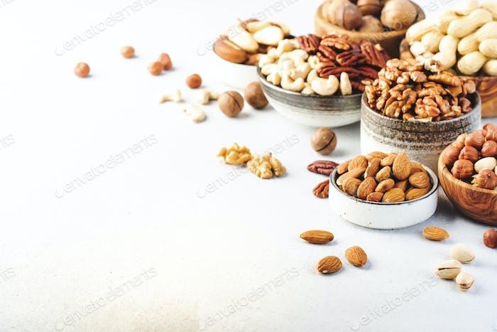 Assortment of nuts in bowls. Cashews, hazelnuts, walnuts, pistachios, pecans, pine nuts