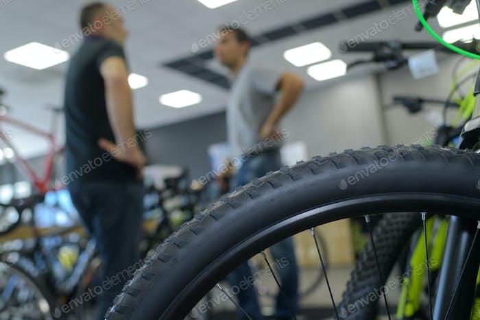 Men talking in bicycle showroom