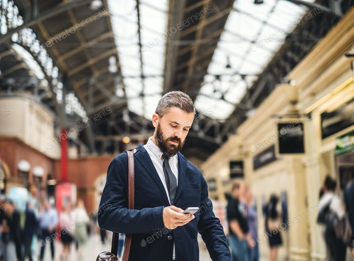 Businessman with smartphone on the trian station in London, texting.