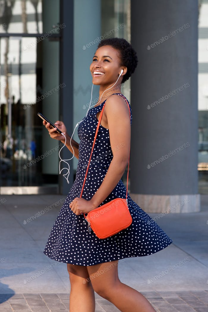 smiling black woman walking and listening to music on earphones