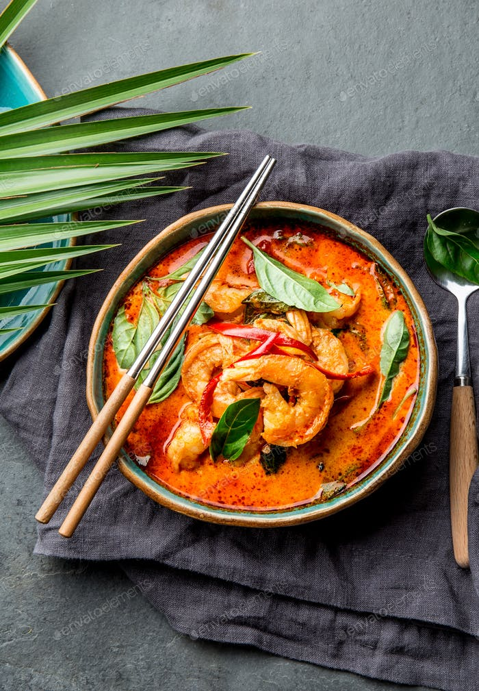 THAI SHRIMPS RED CURRY. Panaeng Curry in blue plate on gray background.