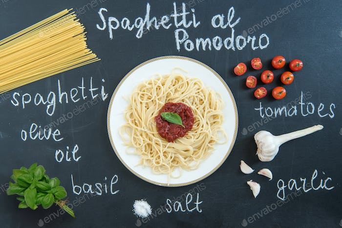 Top view of spaghetti with sauce, basil and ingredients on black