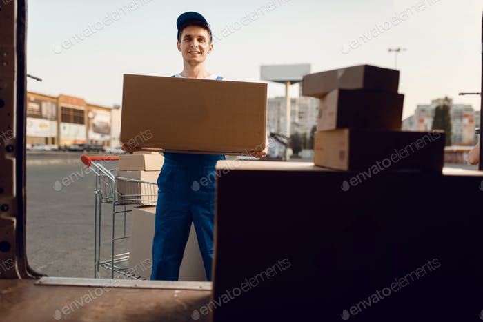 Loader in uniform holding box, delivery service