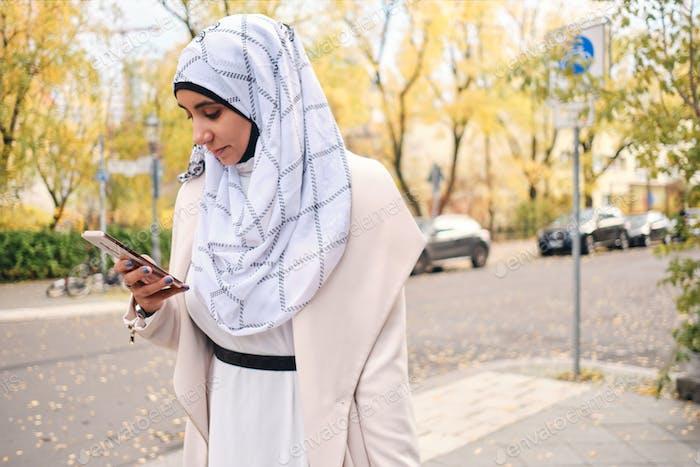 Junge attraktive arabische Frau im Hijab aufmerksam mit Smartphone auf der Stadtstraße