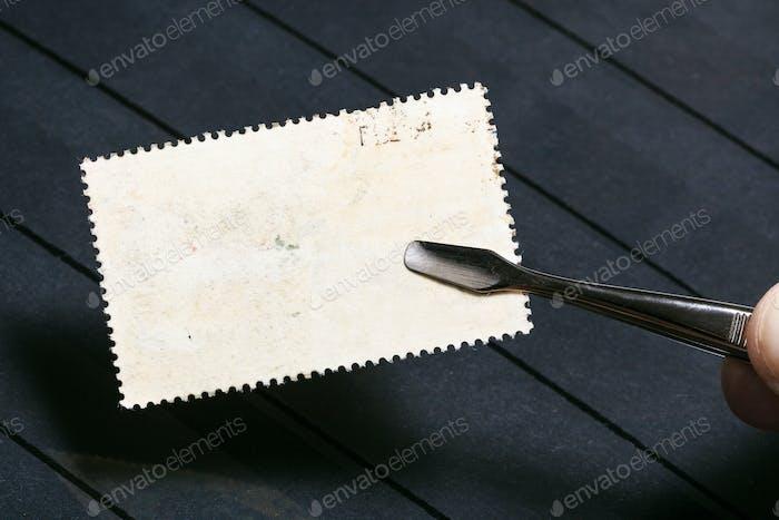 tongs keeps postage stamp with unused back side