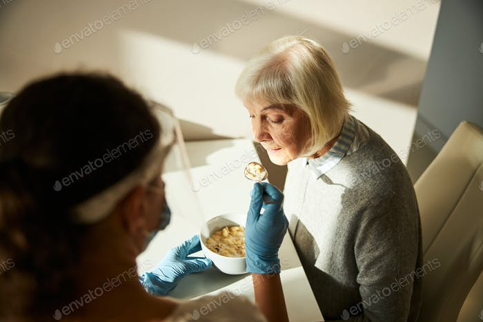 Carer in latex gloves feeding an aged lady