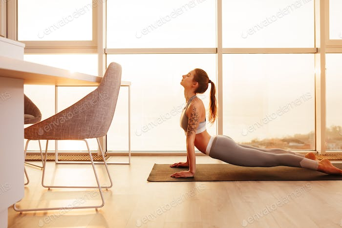 Lady in sporty top and leggings practicing yoga on yoga mat at home with big beautiful windows