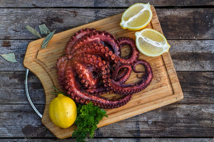 Boiled octopus ready for serve with lemon and parsley on wooden board