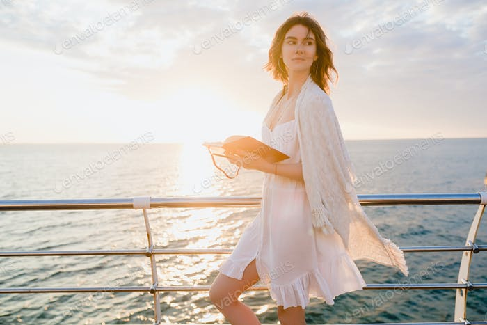 beautiful woman in white summer dress by the sea