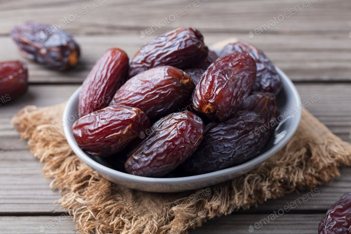 Fresh Medjool Dates in Bowl. Grey Wooden Background. Close up.