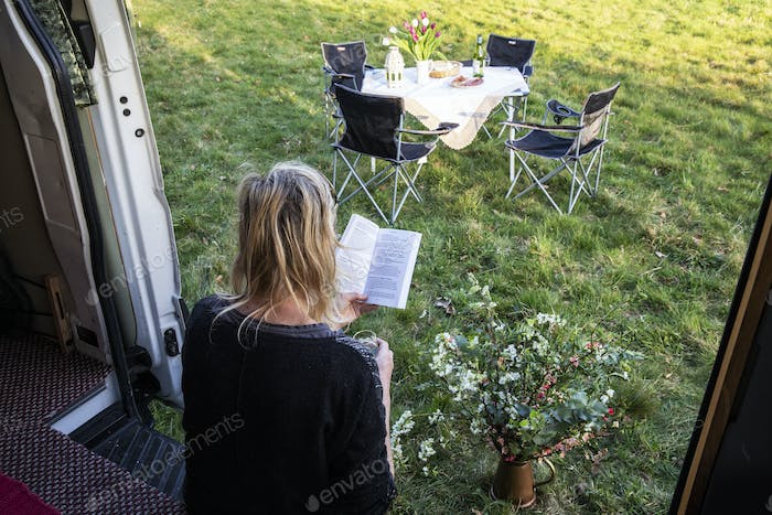 High angle rear view of woman sitting in door of camper van parked on a meadow, reading a book.