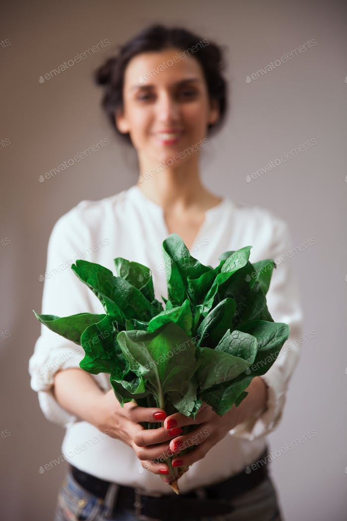 Young woman hands with spinach