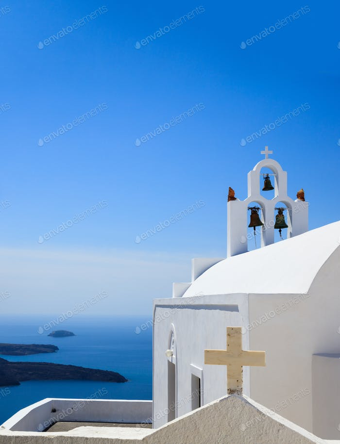 Santorini, Greece. White church and bells against blue sea and sky background.