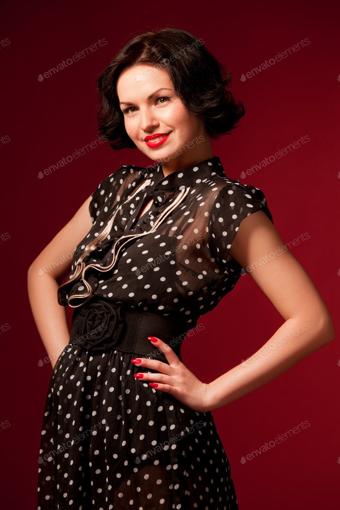 Young woman in black vintage dress standing over red background