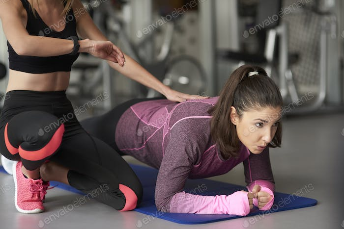 Personal trainer with woman at the gym