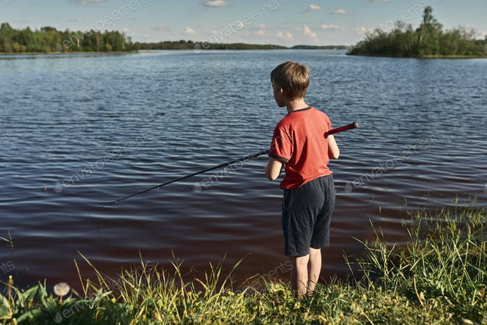 Children fishing on the shore of a large lake.