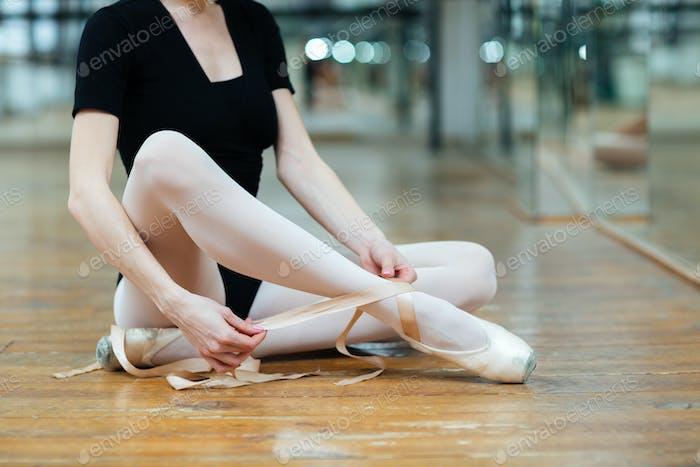 Ballerina tying pointe shoes in ballet class