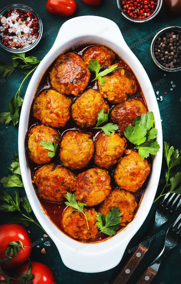 Meatballs with tomato sauce and spices in baking dish on blue kitchen table