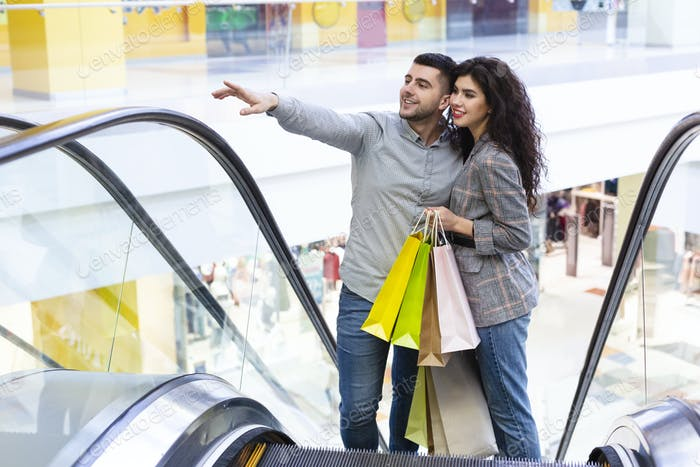 Happy young couple with shopping bags rising on escalator