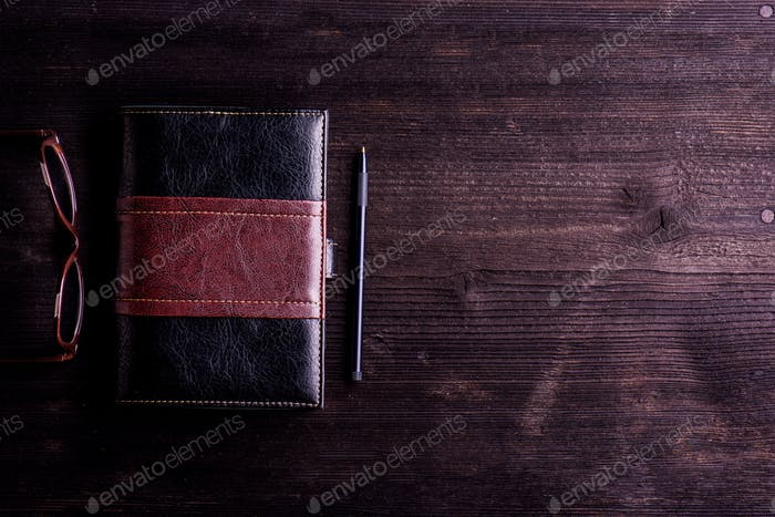 Book, eyeglasses and pen laid on old wooden table