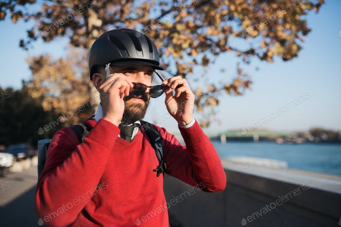 Businessman commuter with bicycle helmet and sunglasses on the way to work in city.