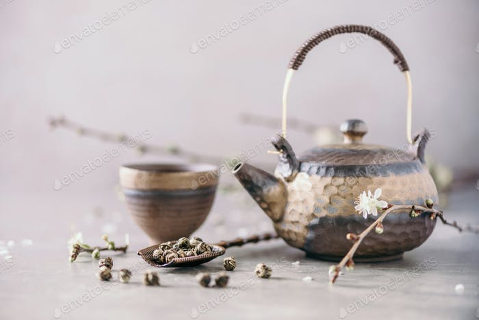 Black and brown iron teapot and tea cups, blossom flowers cherry branch on gray background. Top view