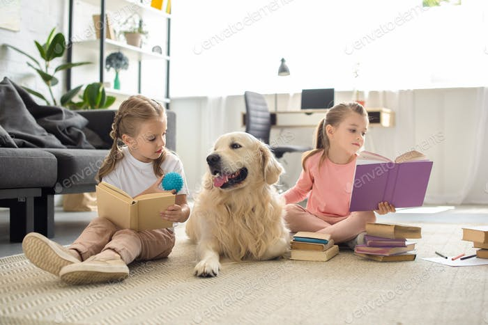 little sisters reading books with golden retriever dog near by at home
