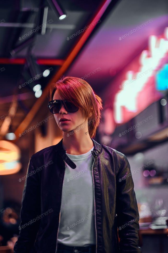 Stilvolle Rothaarige Mädchen stehen in der Nacht auf der Straße. beleuchtete Schilder, Neon, Lichter