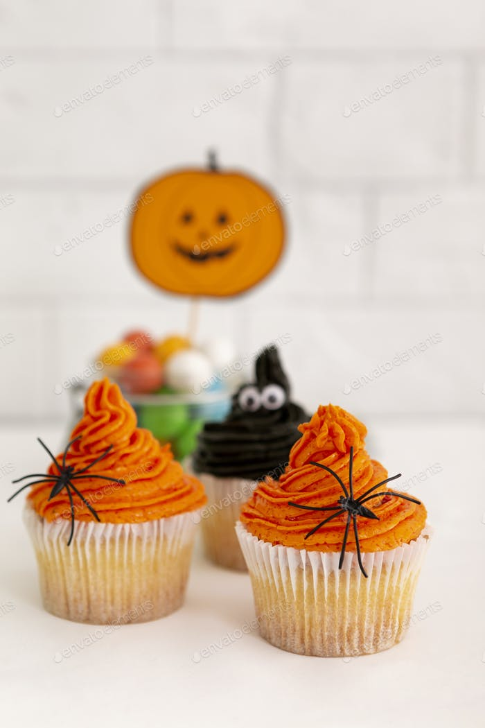 Scary or cute Halloween cupcakes of pumpkin on background