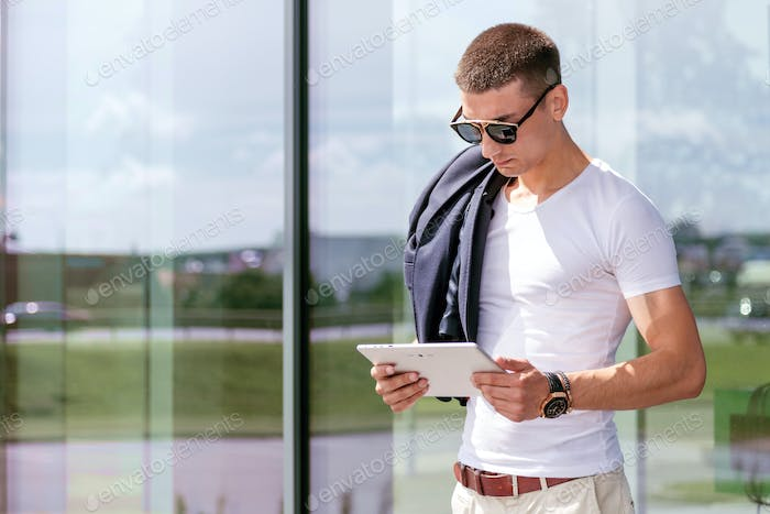 Young fashionable wearing a freelancer working on the tablet