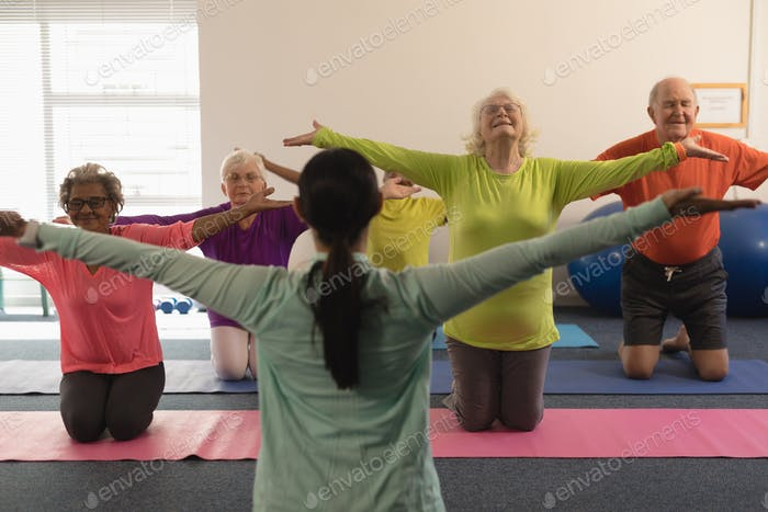 Young female trainer assisting senior people with tensioned arms in fitness studio