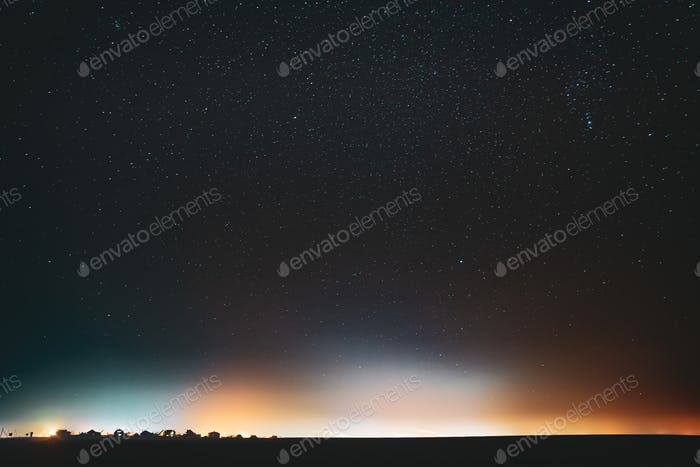 Night Starry Sky With Glowing Stars Above Countryside Town Landscape. Rural Field Meadow In Early